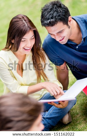 Couple of college students studying outdoors looking happy