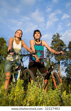 Couple of cyclers on their bikes in the countryside on hot summer day - stock photo