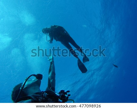 Couple of divers. Hands reaching out to one another, almost touching. Rangiroa, French Polynesia.