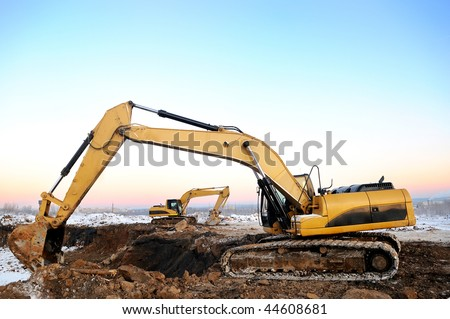 couple of excavator loaders at construction site with raised bucket over blue sky in winter