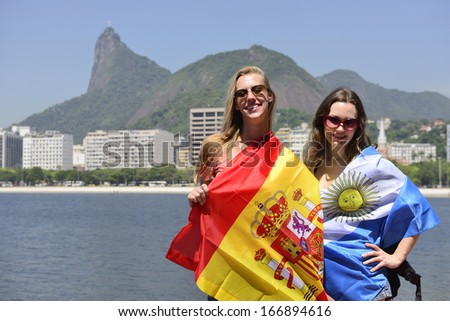 Couple of female sport fans holding the Spanish and Argentinian flag in Rio de Janeiro with Christ the Redeemer in the background. - stock photo