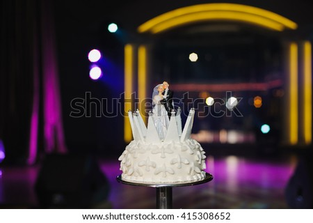 Couple of figurines on top of wedding cake. Spotlights light on the background. - stock photo