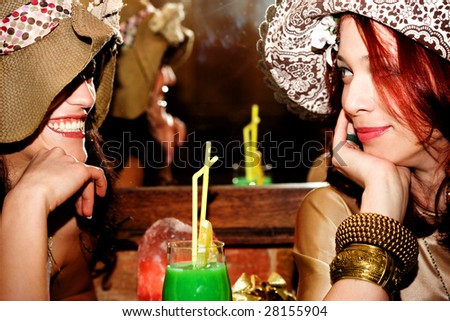 couple of girlfriends with romantic hats in cafe - stock photo
