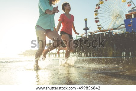 Couple of girls running in the water and having fun together