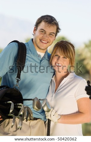 Couple of golfers embracing on golf course, (portrait)