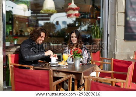 Couple of good friends met by chance in the street sat sidewalk cafe at cool autumn day  happily discuss all the latest news in their lives while they enjoying cup of coffee and fresh juice breakfast - stock photo