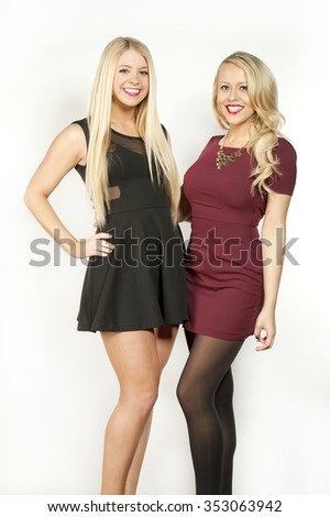 Couple of gorgeous young hip blonde girls in a studio setting while wearing black and red outfits on a white background.
