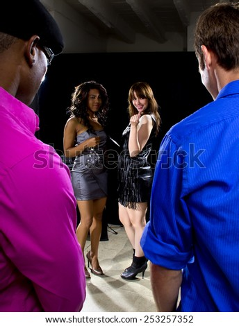 couple of guys trying to pickup women at a nightclub - stock photo