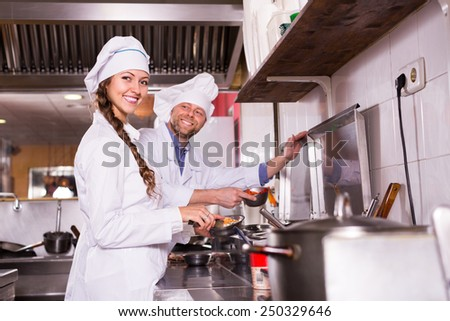 Couple of happy smiling cooks working together at kitchen in take-away restaurant  - stock photo