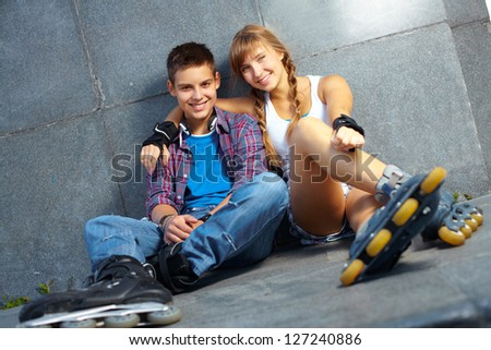 Couple of happy teens on roller skates looking at camera - stock photo