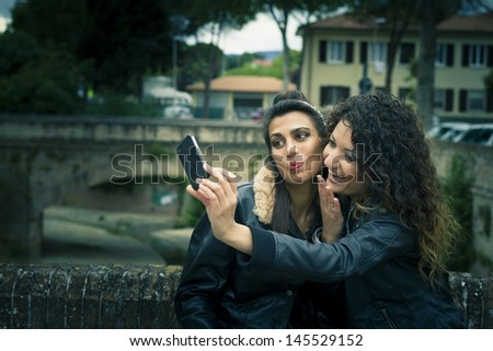 Couple of happy women play with a smartphone - stock photo