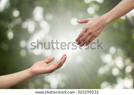 couple of helping human hand and hand praying on blurred green nature background,spiritual of life ideal.support sustaining of humanity and religious:love togetherness:heal/help/assistance conceptual - stock photo
