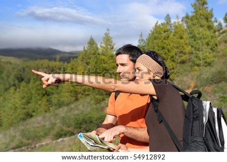 Couple of hikers finding their way - stock photo