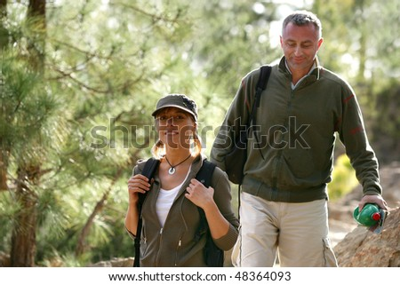 Couple of hikers in the forest - stock photo