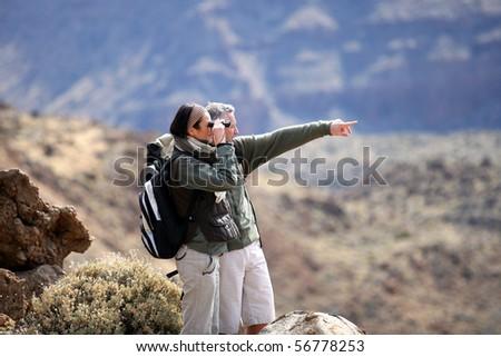 Couple of hikers looking away through binoculars - stock photo