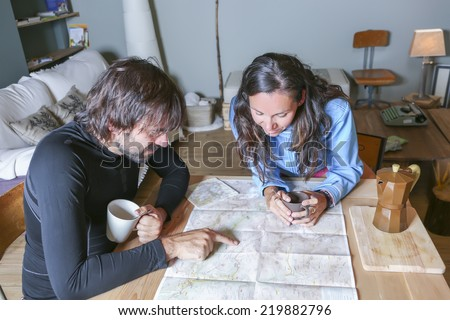 couple of hikers planning the route sitting around a table pointing the route in a map in a welcoming shelter - focus on the young woman - stock photo