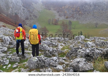 Couple of hikers scrambling on rock covered valley in misty morning - stock photo