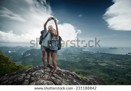 Couple of hikers taking selfie from top of the mountain with valley view on the background - stock photo
