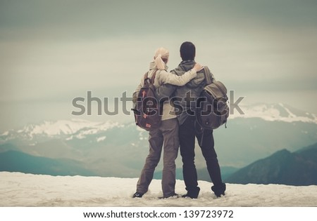 Couple of hikers with backpacks looking over mountains view - stock photo