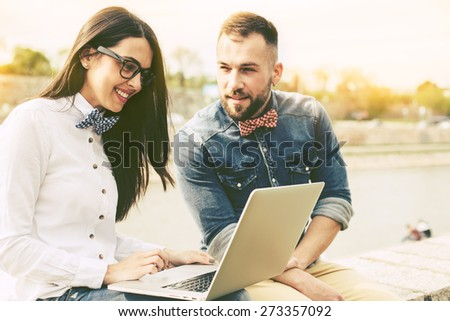 Couple of hipster friends, young man and woman, using laptop in the city - stock photo