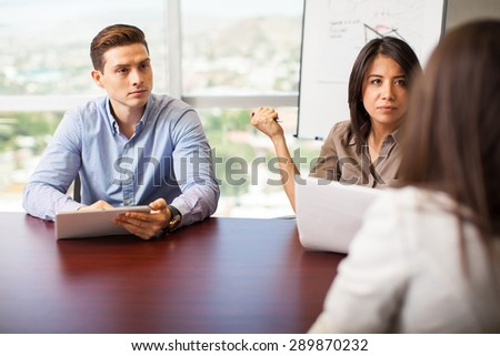 Couple of human resources workers interviewing a woman for a job position - stock photo