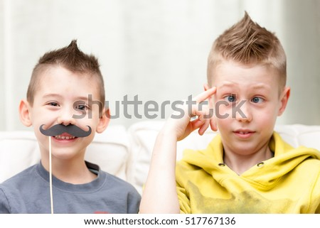 couple of little brothers making funny faces with fake moustaches