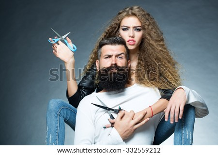 Couple of long-haired young beautiful woman holding two pairs of scissors sitting behind handsome bearded grey-haired man with moustache both looking forward on grey background, horizontal picture - stock photo
