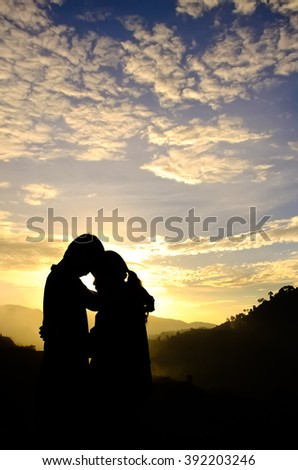 Couple of love stand and hug and kiss each other in fog on the mountain at the morning and sunrise behind them. Silhouette side view.