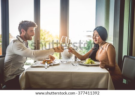 Couple of lovers having a romantic lunch in a restaurant, toasting wine glasses to celebrate anniversary - stock photo