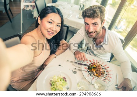 Couple of lovers in a restaurant and taking a picture - Romantic date in a classy restaurant at sunset - Two attractive friends having fun in a bistro bar - stock photo