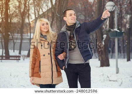 Couple of lovers in the city park a love story. Winter, tourism, leisure, love story. Joint walk through the winter town. Romantic happy urban couple Stylish urban young man and woman on travel Europe - stock photo