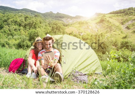 Couple of lovers is smiling using their tablet during the camping - concept about technology and camping - caucasian people - stock photo