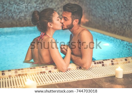 Couple Of Lovers Kissing In Spa Swimming Pool