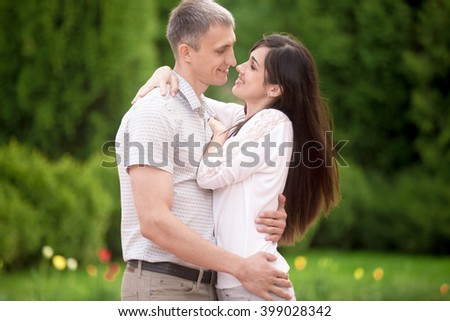 Couple of lovers on a date in park, standing face to face, young man tenderly embracing his happy smiling girlfriend, about to kiss - stock photo