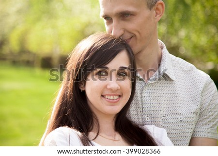 Couple of lovers on a date, young man tenderly hugging his happy smiling girlfriend