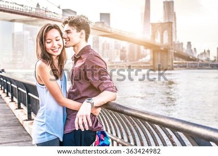Couple of lovers on a romantic date in New York - Woman hugging his boyfriend and he whispers something in her ear - Beginning of a romantic relationship - stock photo
