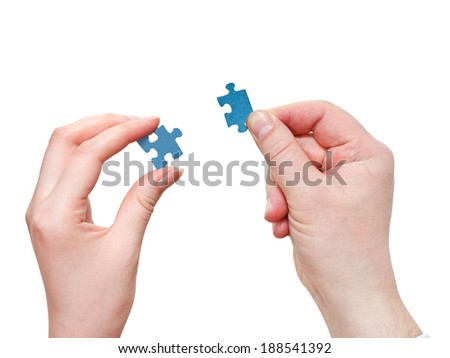 couple of male and female hands holding little puzzle pieces isolated on white background