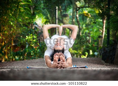 Couple of man and woman in white cloth doing yoga in the garden. Woman looking at camera and smiling