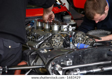 Couple of mechanics repairing an engine of a race car.