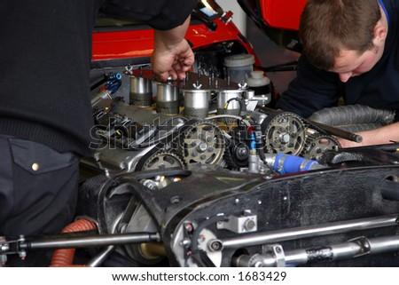 Couple of mechanics repairing an engine of a race car. - stock photo