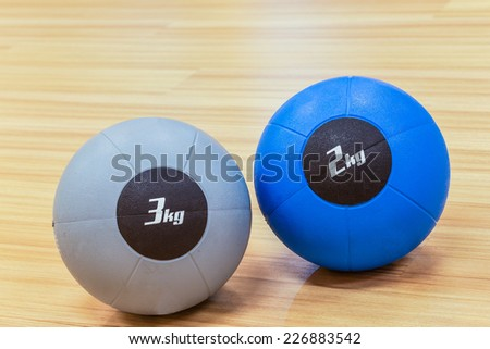 couple of medicine weight ball on wooden floor - stock photo