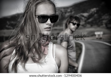 Couple of modern young people posing on a road over picturesque landscape. - stock photo