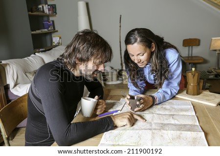 couple of mountaineers sitting having coffee planning the route looking at a map in a shelter - focus on a young woman - stock photo