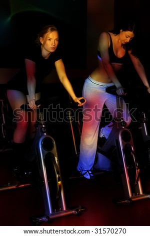couple of nice girls in a gym club with colored light effect