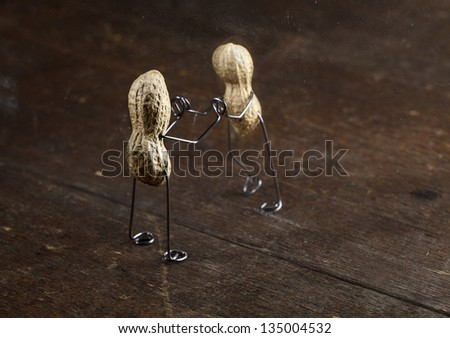 Couple of Peanut People being kept apart by a glass wall - stock photo