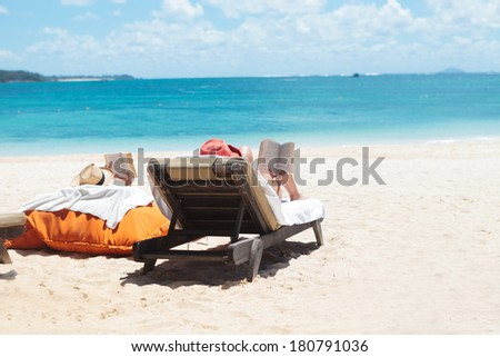 couple of people reading while sunbathing on the beach of mauritius - stock photo