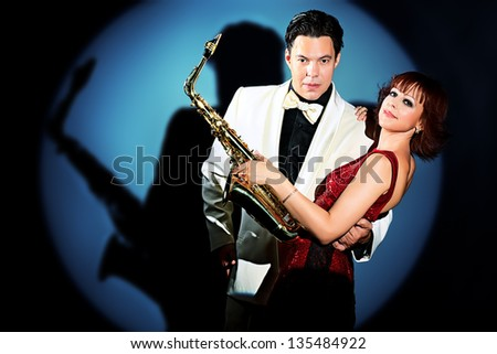 Couple of professional musicians in retro style posing in costumes at studio. - stock photo