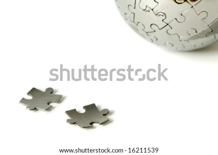 couple of puzzle pieces next to a puzzle world - stock photo