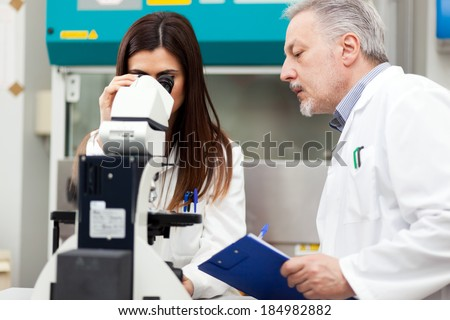 Couple of scientist researching in a laboratory - stock photo