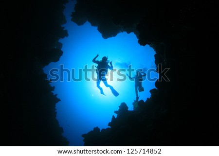 Couple of Scuba Divers descend into an underwater cavern - stock photo